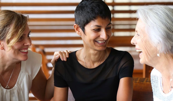 Three beautiful women of different ages and nationalities laughing together taken from the Esoteric Women's Health website